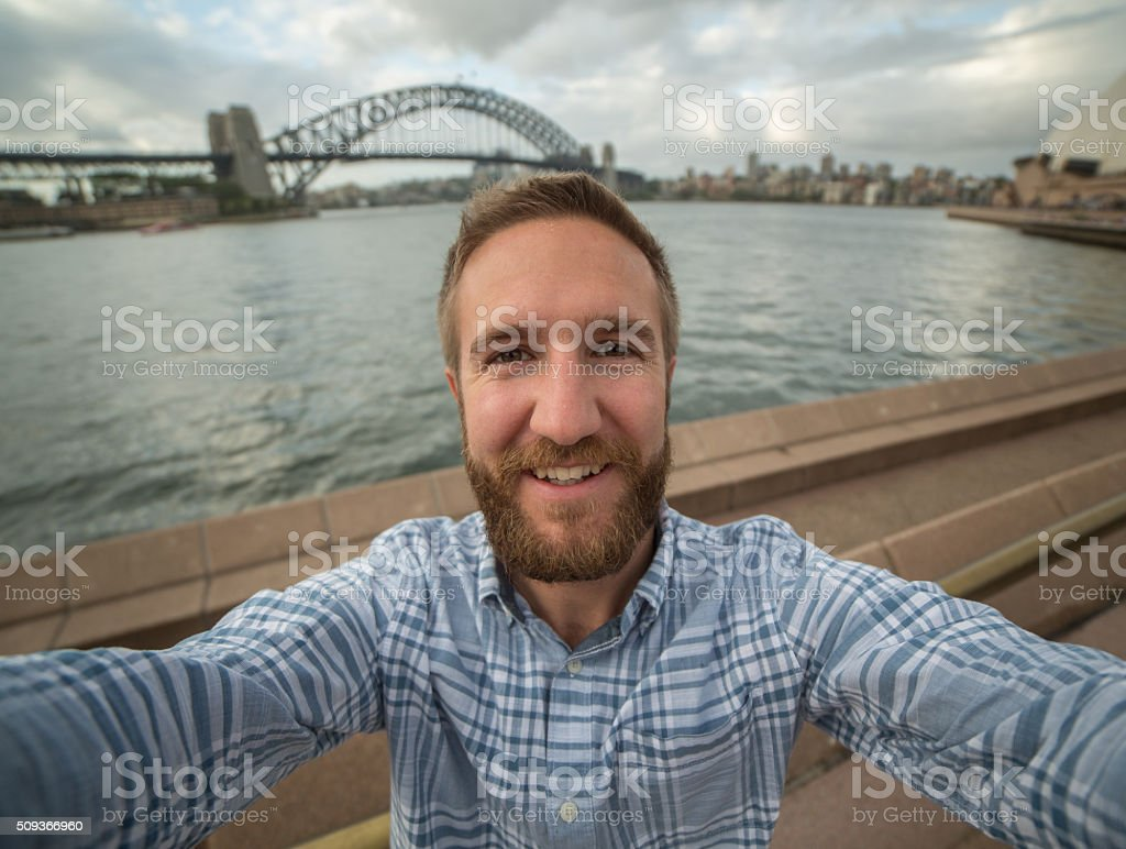 Young man in Sydney harbour, takes a selfie portrait stock photo