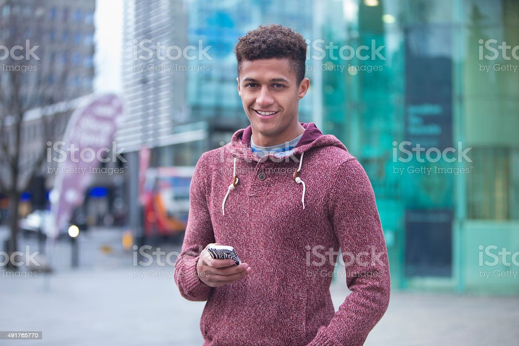 Young man in the city with a smartphone stock photo