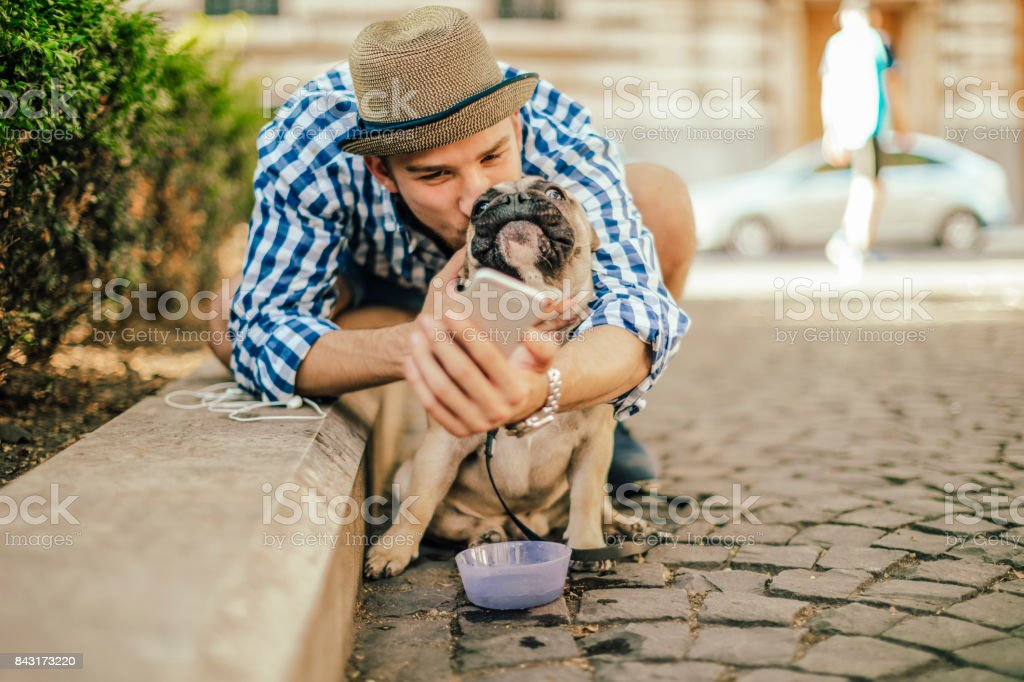 Young man in the city with his french bulldog stock photo