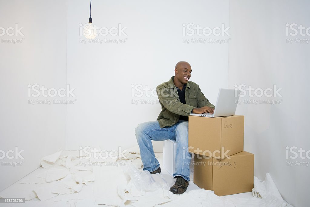 Young man in the middle of moving types on laptop royalty-free stock photo