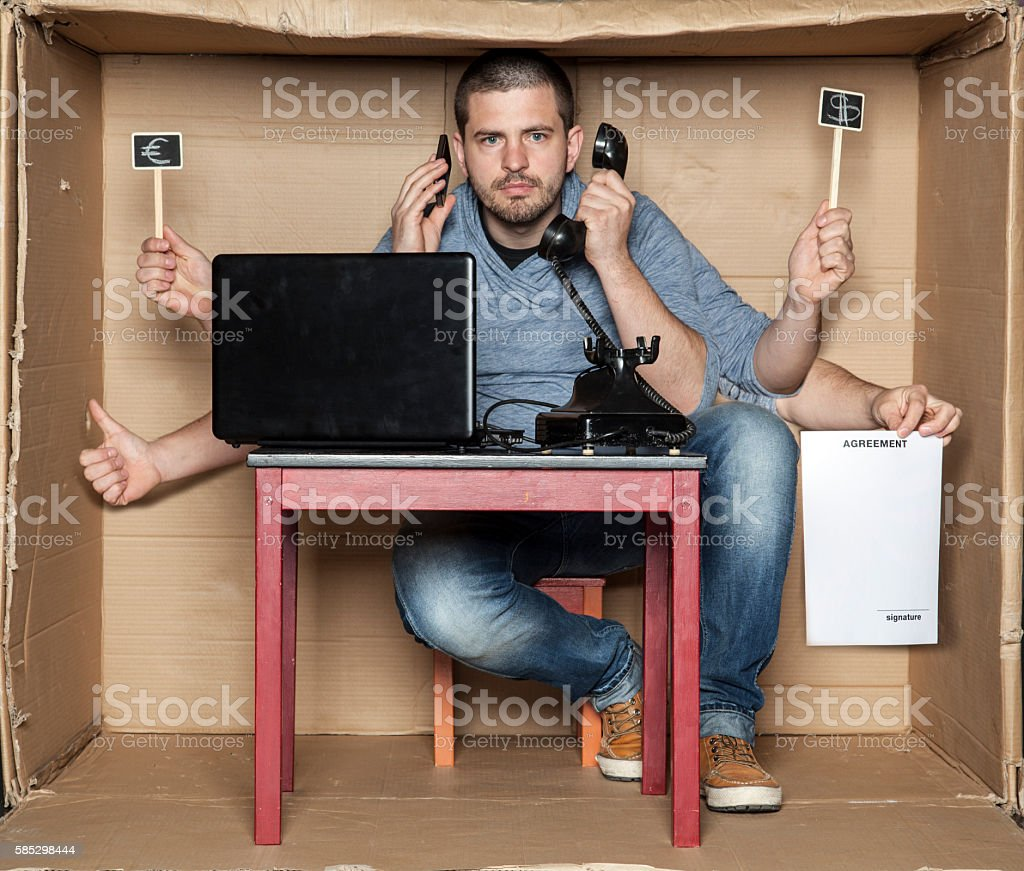 young man in the office box is a very multitasking stock photo