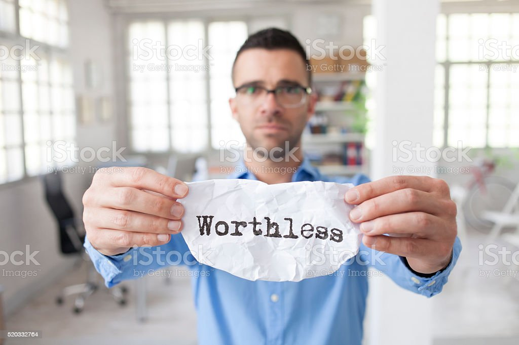 Young man in the office holding sign 'worthless' stock photo
