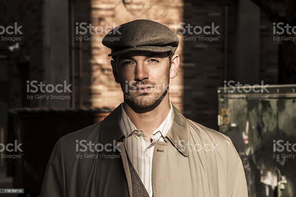 Young Man in Trench Coat and Driving Cap stock photo