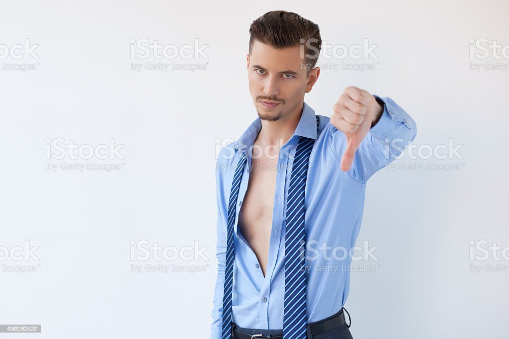 Young Man in Unbuttoned Shirt Showing Thumb Down stock photo