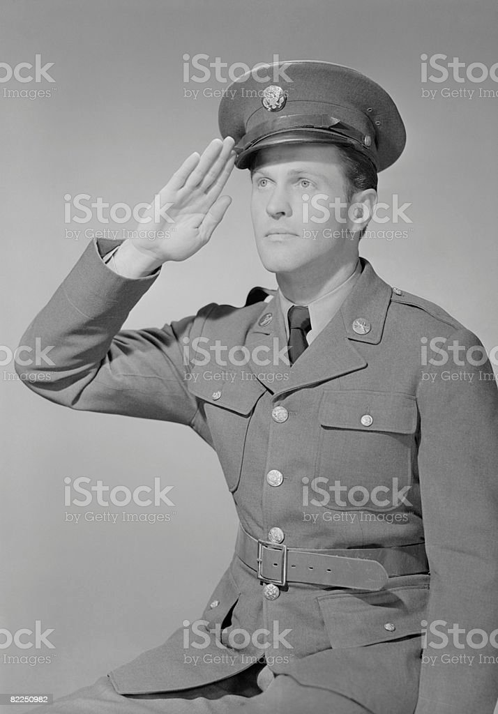 Young man in uniform saluting stock photo