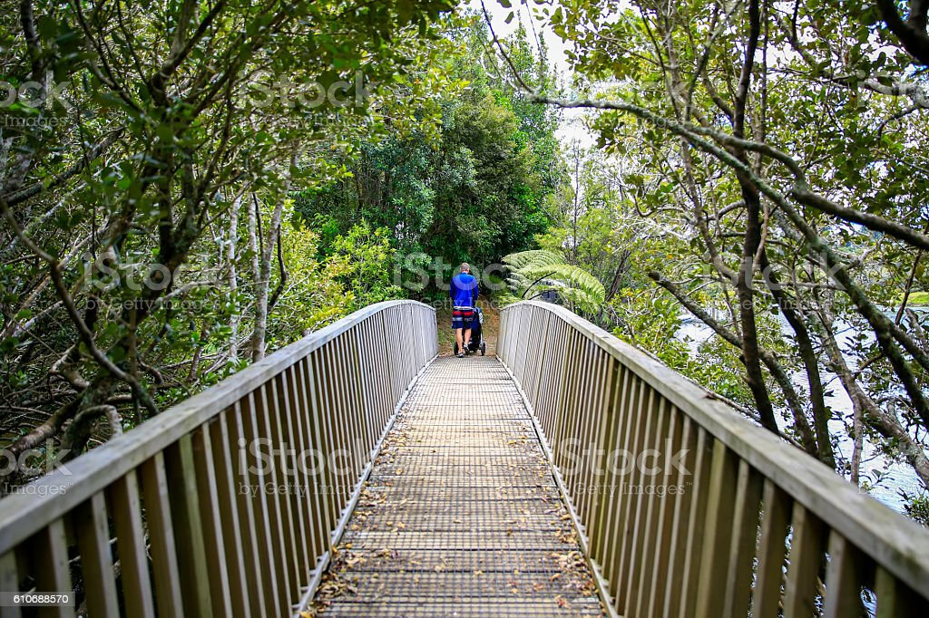 Young man in with baby stroller crossing the bridge stock photo