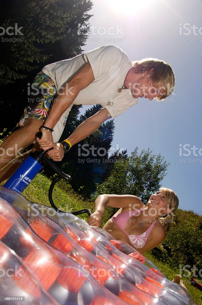 Young man inflating air bed, teenage girl holding hose stock photo
