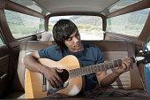 Young man inside car playing guitar