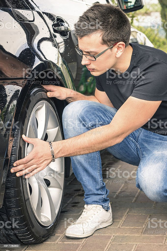 Young man inspecting luxury car at second hand sale stock photo