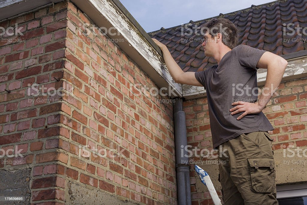 Young man inspecting the roof of an old house royalty-free stock photo
