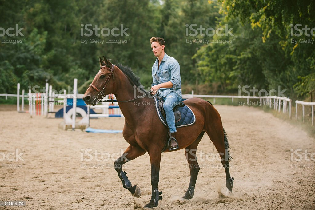 Young man is enjoying horseback riding in nature. stock photo