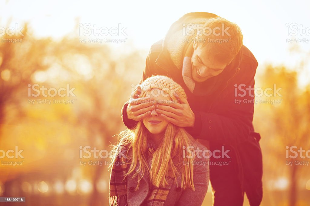 young man is giving a surprise to his girlfriend stock photo