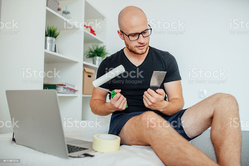 Young man is holding painting tools and looking at them. stock photo