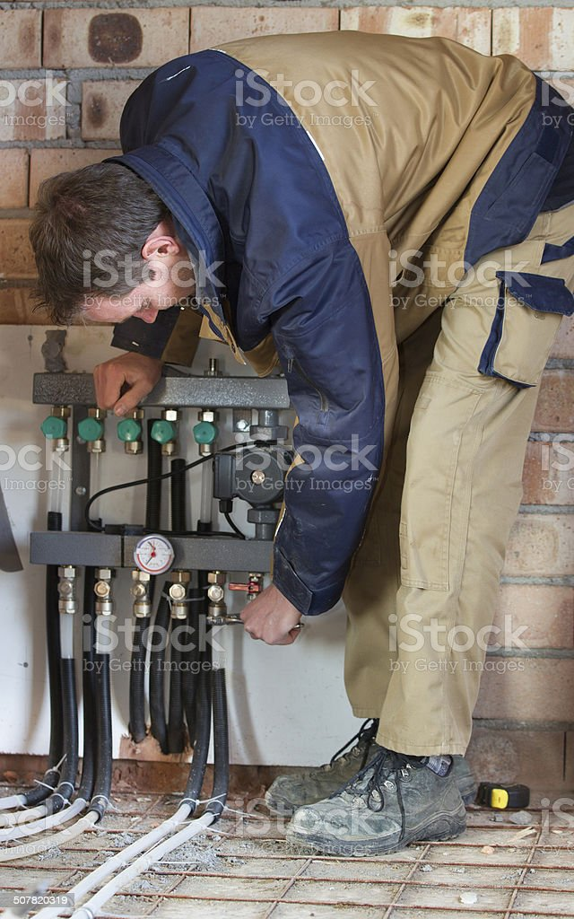 Young man is installing the heating system stock photo