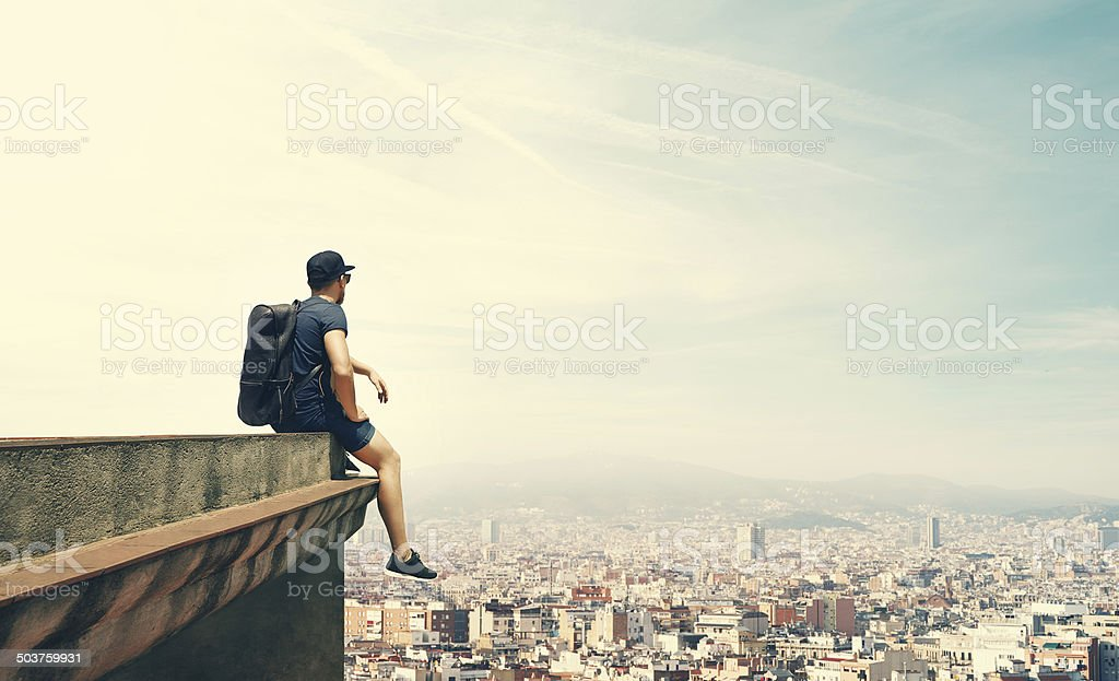 Young man is sitting on a roof and looking city stock photo