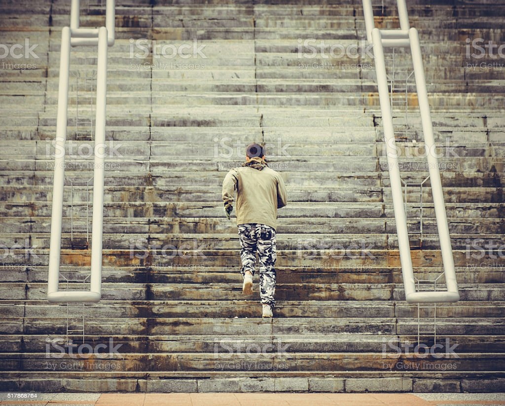 Young man jogging on stairs. stock photo