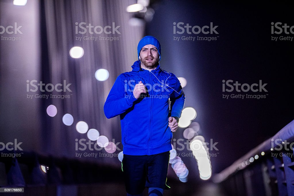 Young man jogging through the city at night stock photo