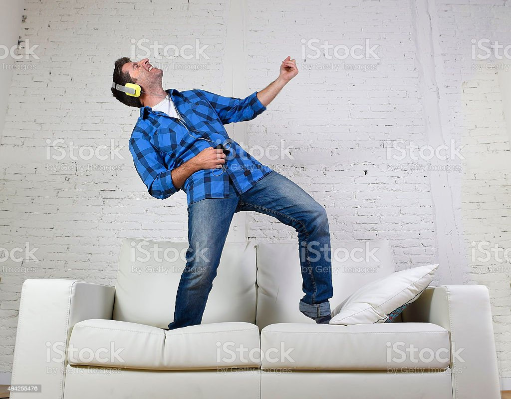 young man jumped on couch listening to music with headphones stock photo