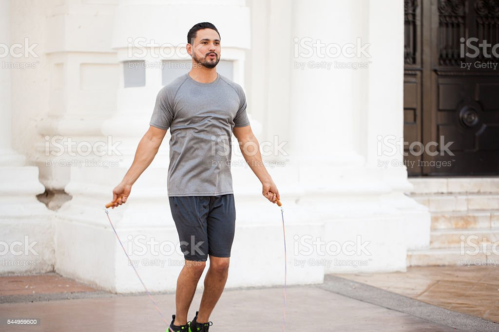 Young man jumping a rope outdoors stock photo