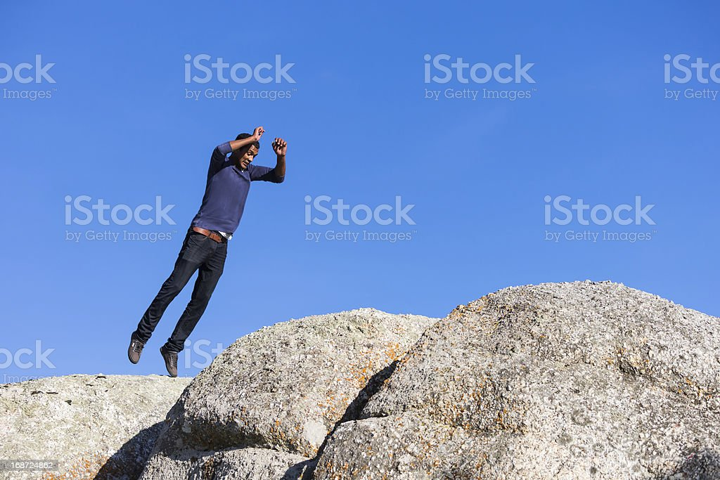 Young Man Jumping Across Boulders stock photo