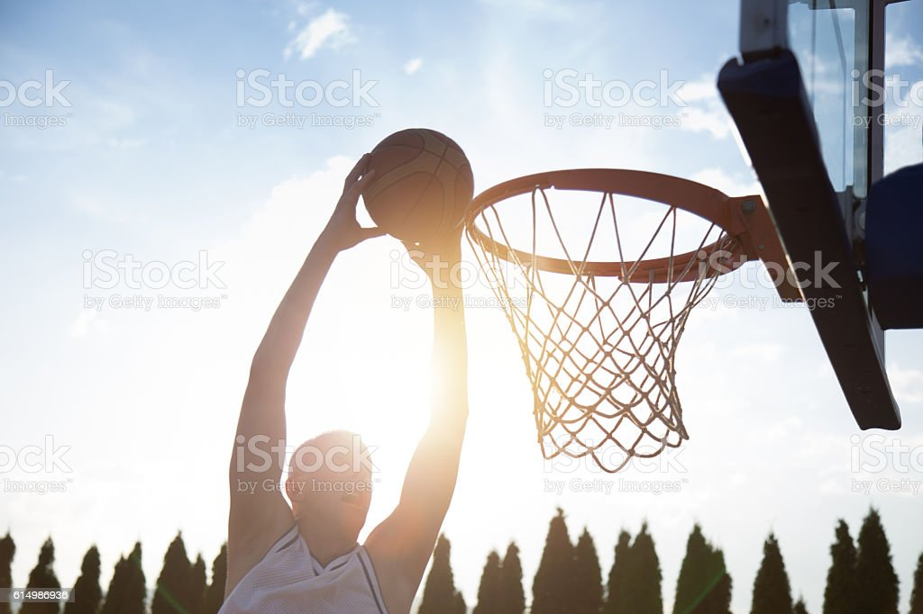Young man jumping and making a fantastic slam dunk stock photo