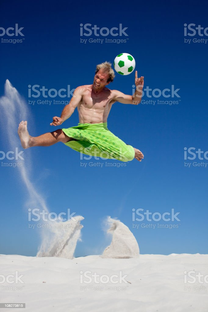 Young Man Jumping and Playing Soccer on Beach royalty-free stock photo