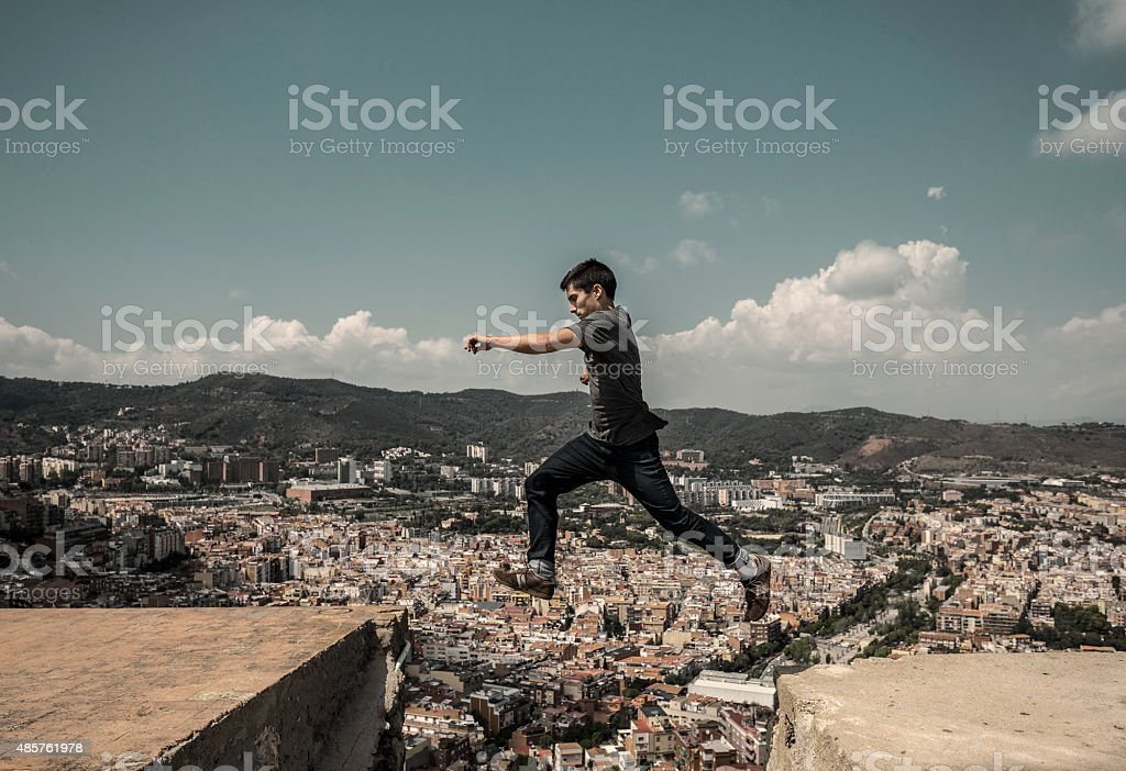 Young man jumping and  practicing parkour in the city stock photo