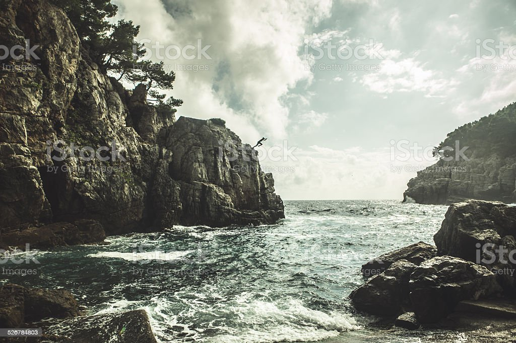 Young man jumping from the cliff.Cliff jumping recreation on seaside stock photo