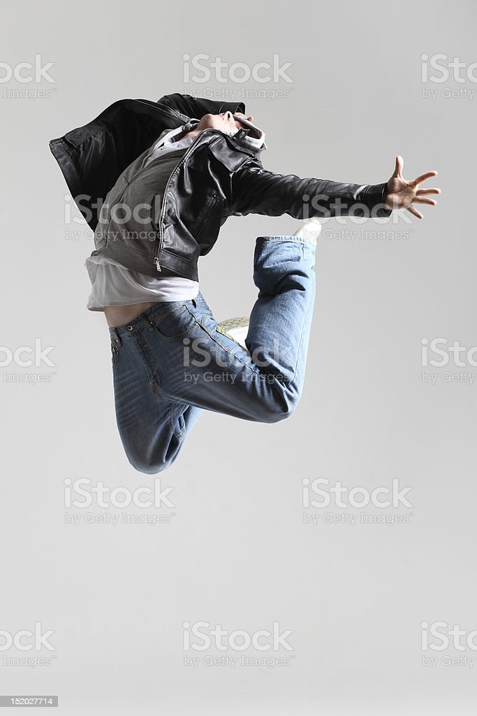 A young man jumping in a very expressive dance move royalty-free stock photo