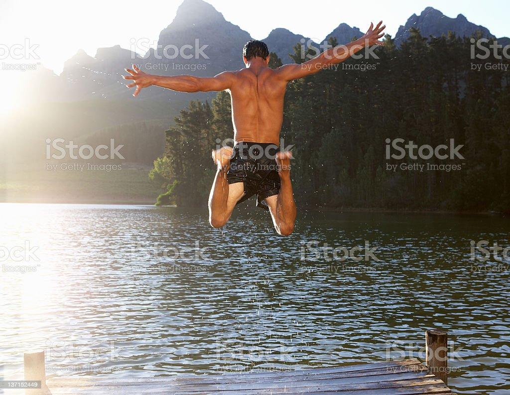 Young man jumping into lake royalty-free stock photo