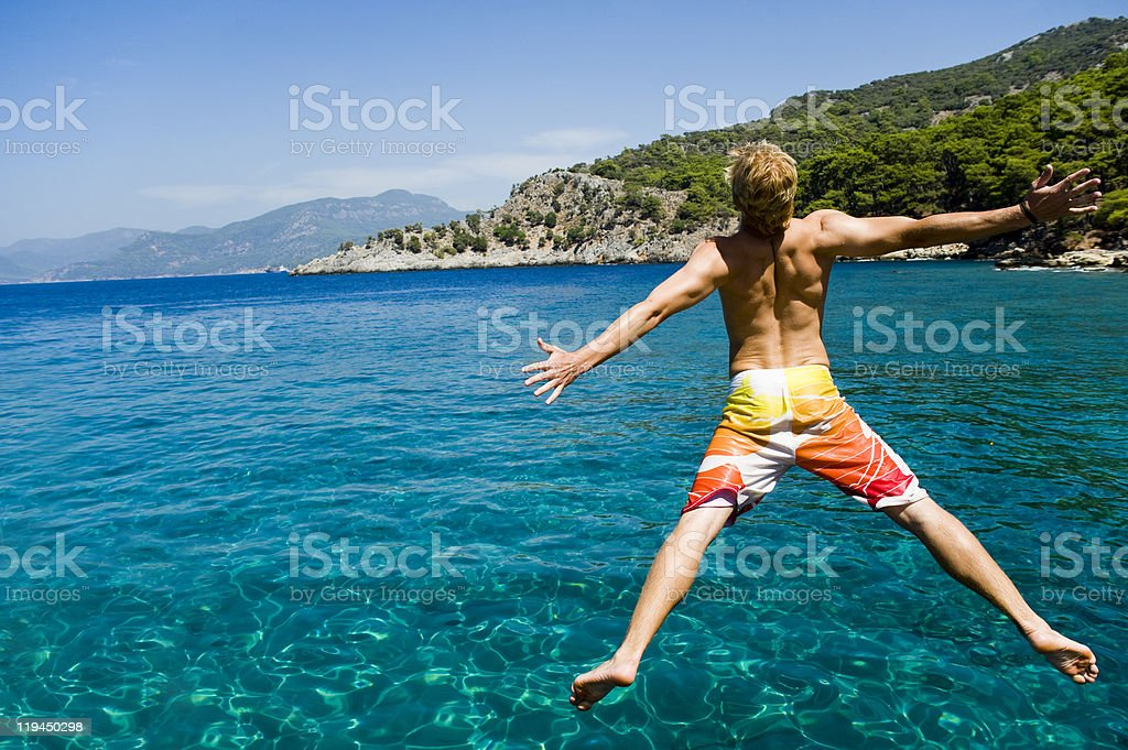 A young man jumping into the blue waters of the sea royalty-free stock photo