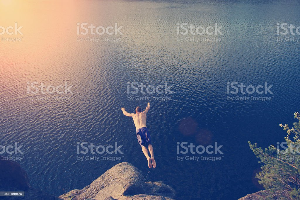 Young man jumping into the river stock photo