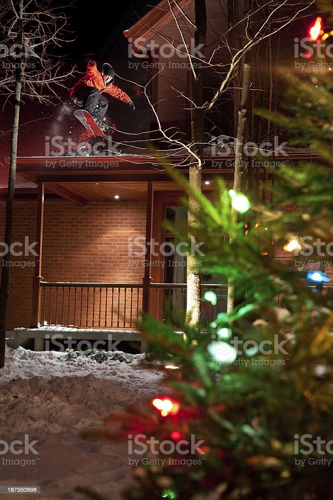 Young man jumping of a roof top in Snowboard. stock photo