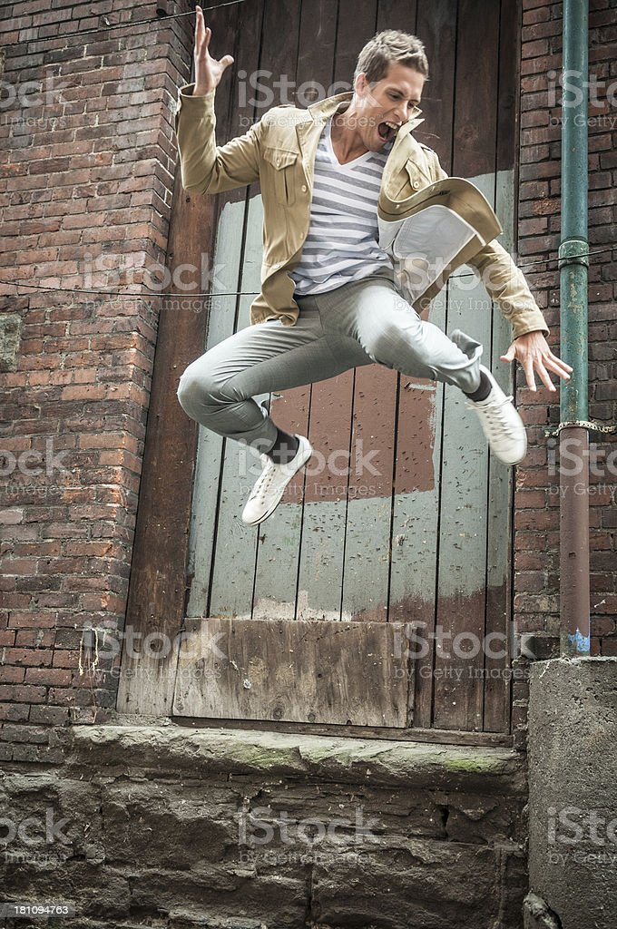 Young man jumping off a building stock photo