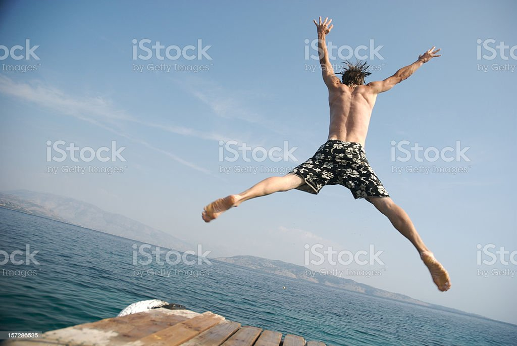 Young Man Jumping Off Pier Into Blue Water royalty-free stock photo