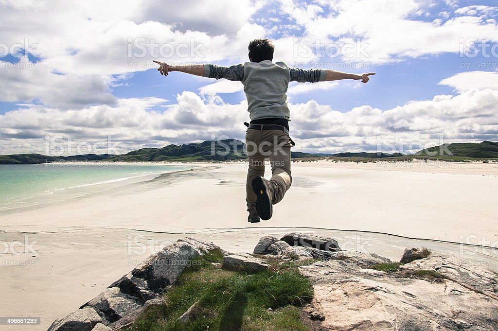 Young man jumping on a cliff with open arms. stock photo