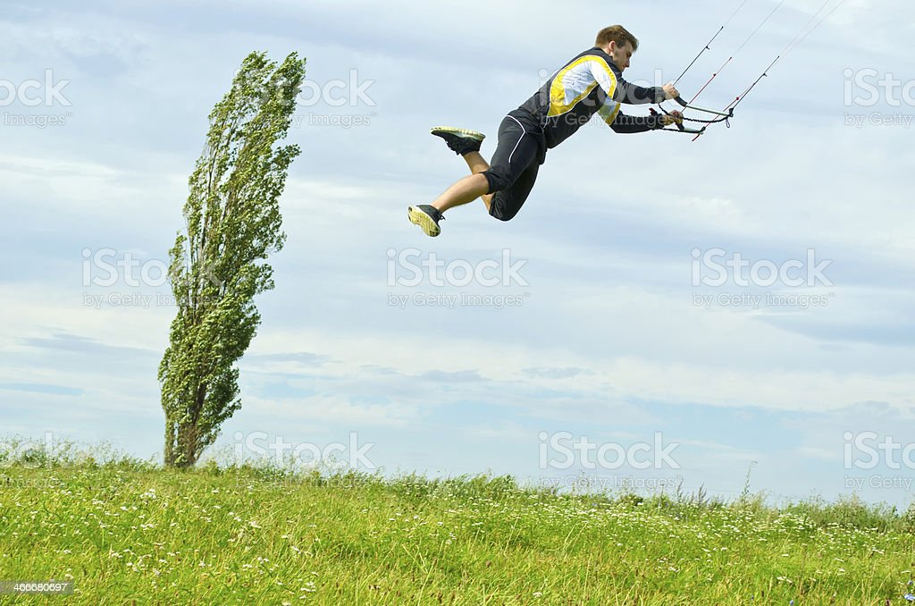 Young man jumping on a kite royalty-free stock photo