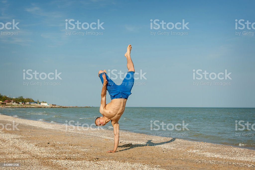 Young man jumping on beach stock photo