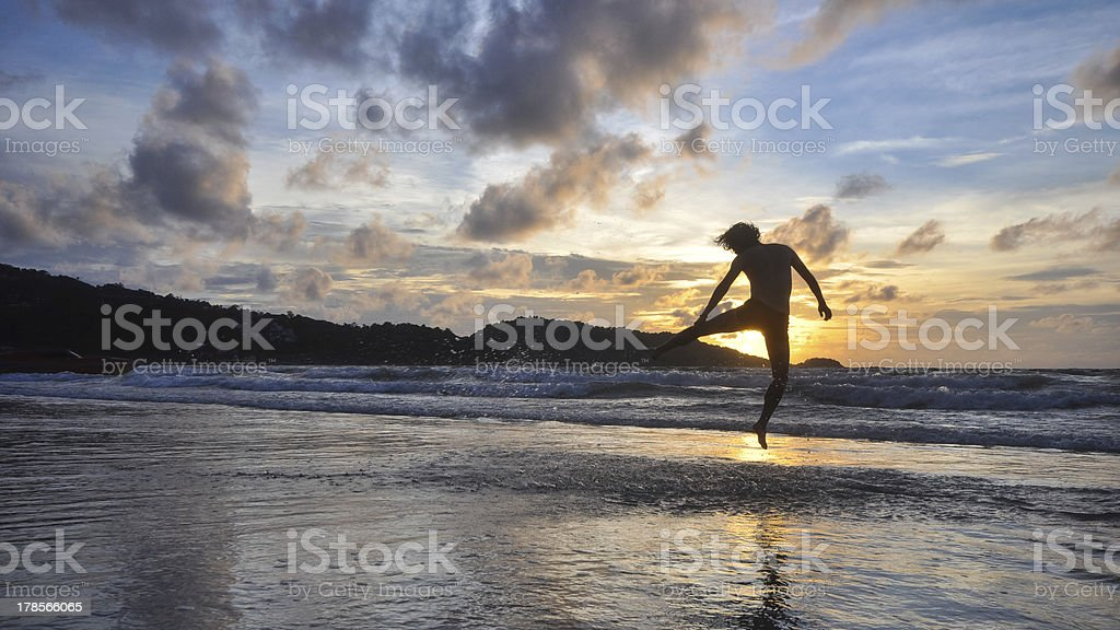 young man jumping on beach when sunset royalty-free stock photo