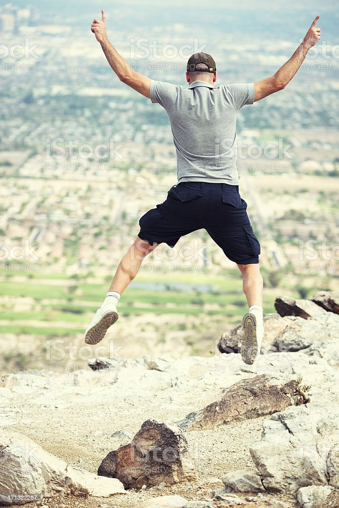 Young man jumping on the rock royalty-free stock photo