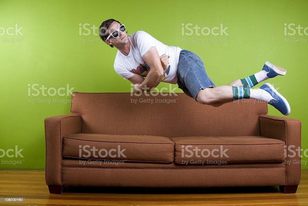 Young Man Jumping Onto Sofa, royalty-free stock photo