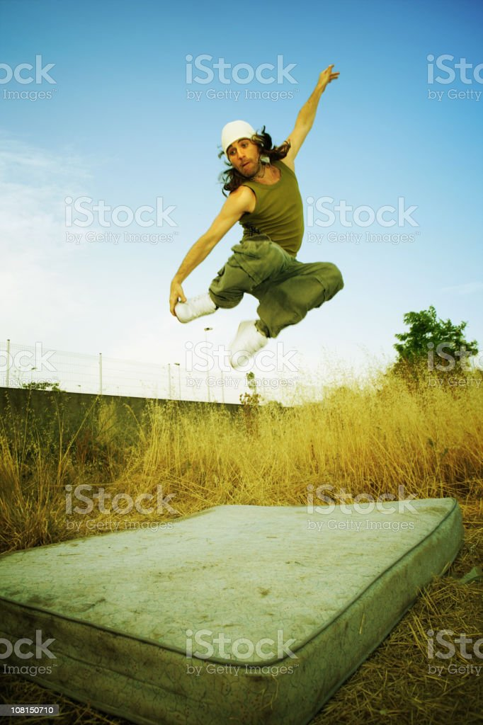 Young Man Jumping Over Old, Abandoned Mattress in Field stock photo