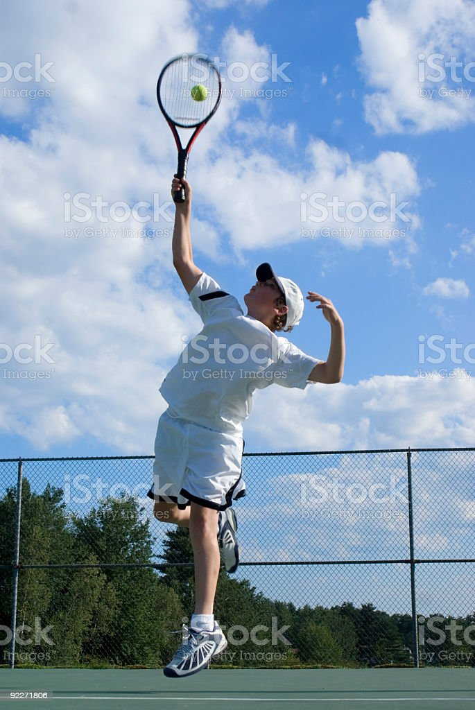 Young man jumping to serve a tennis ball royalty-free stock photo