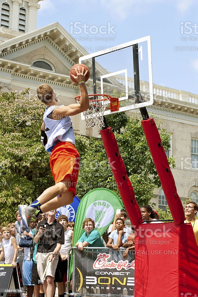 Young Man Jumps Above Rim In Outdoor Slam Dunk Contest royalty-free stock photo
