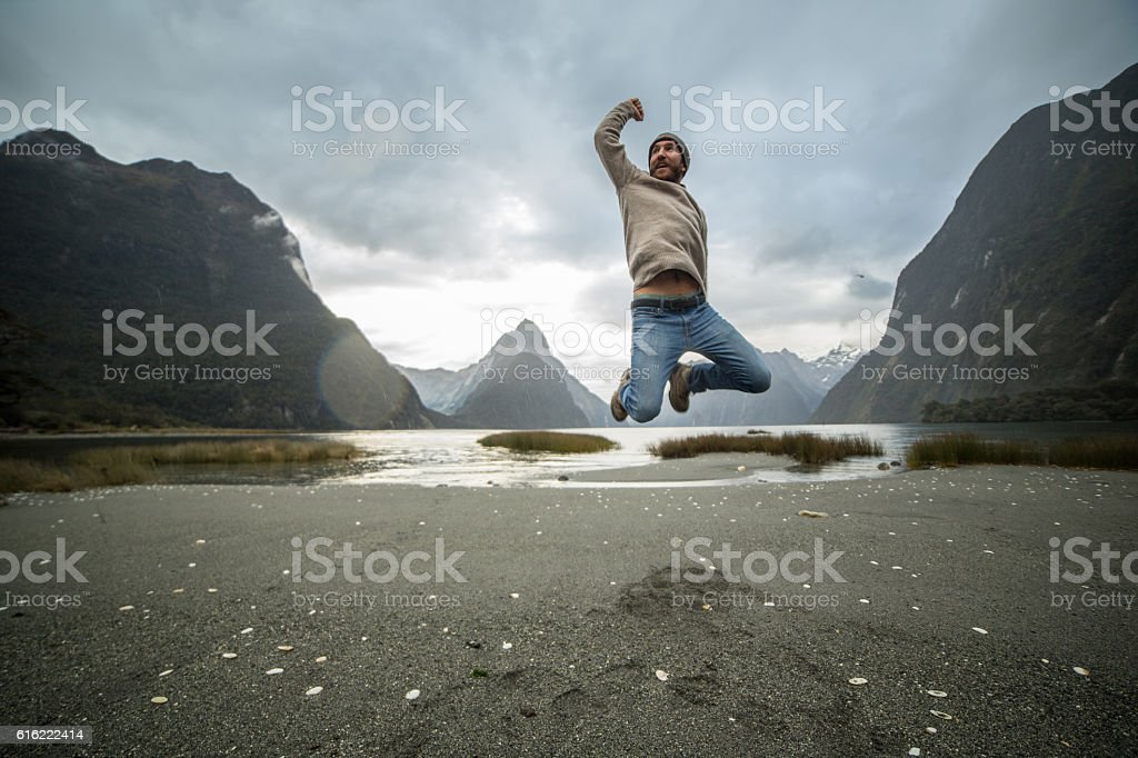 Young man jumps in front of Mitre peak, New Zealand stock photo