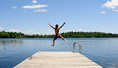 Young man jumps off dock on beautiful summer's day.