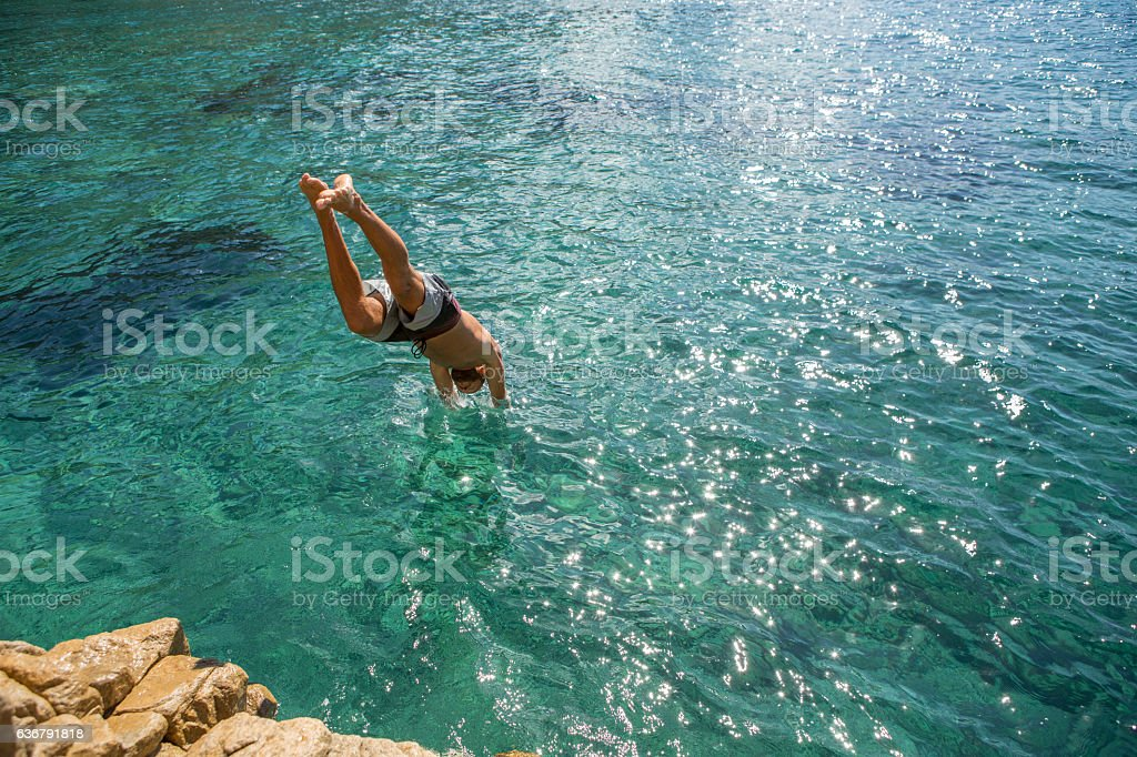 Young man jumps off the cliff into the sea stock photo