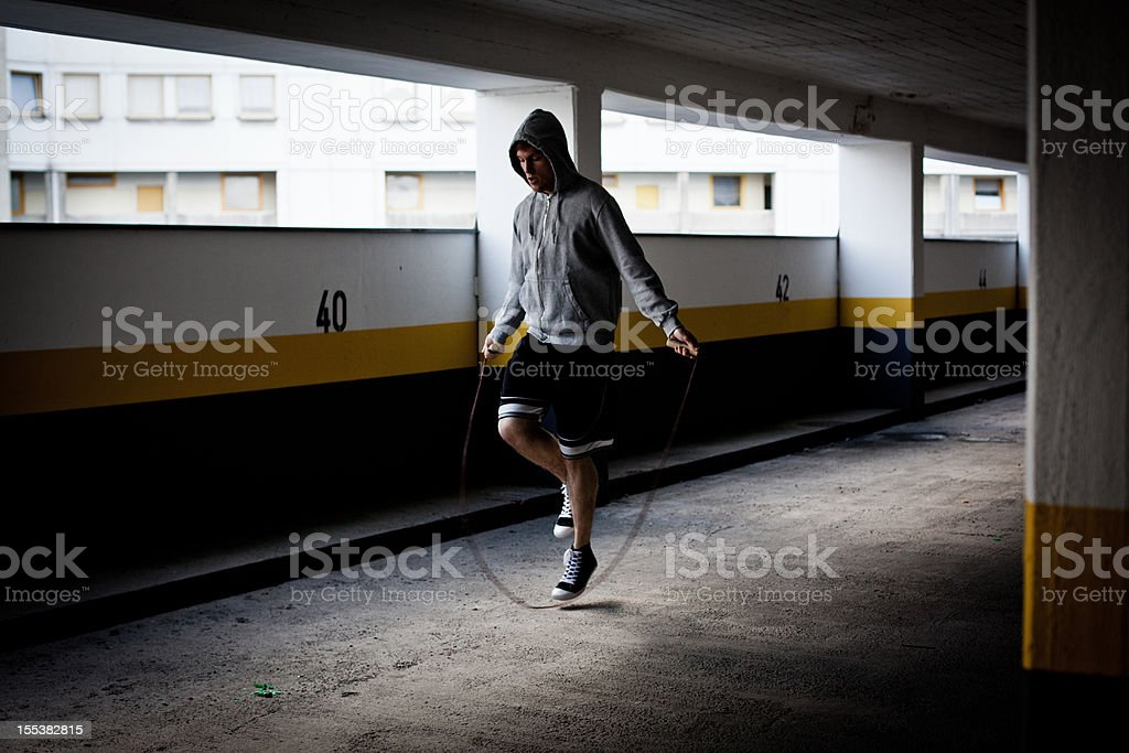 young man jumps rope in empty Parking Garage in Ghetto stock photo