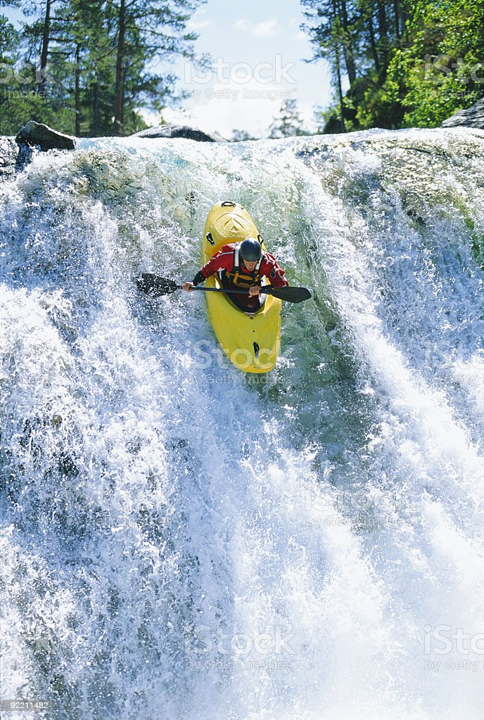 Young man kayaking down waterfall stock photo