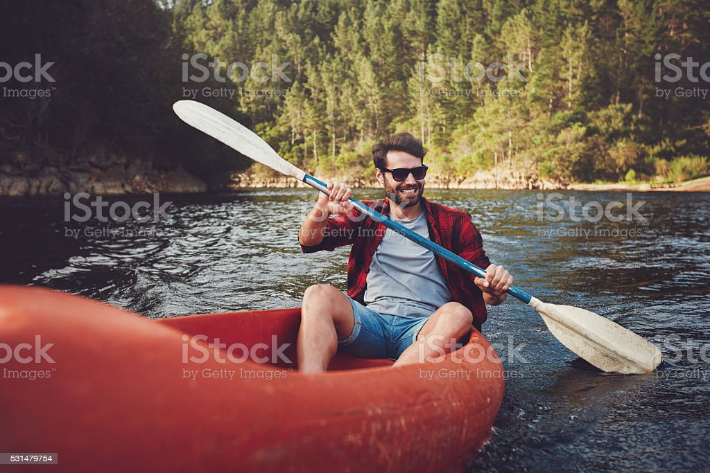 Young man kayaking on a lake stock photo